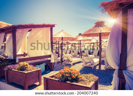 Thatched umbrellas and beach chairs on the beach. Budva, Montenegro, Balkans, Europe. Beauty world. Retro style filter. Instagram toning effect. - stock photo