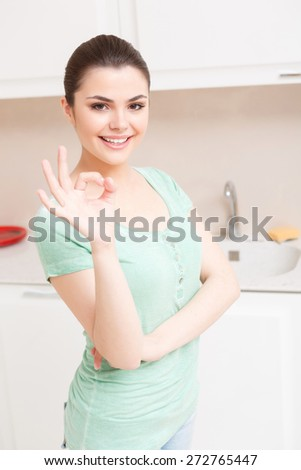 Thats OK. Pleasant young lady standing in white colored kitchen showing that everything is ok