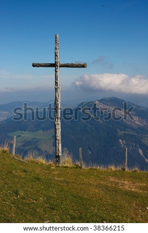 thats the big cross on Rigi mountain, Switzerland. In the background are the Alps, connected with the blue sky with some clouds.