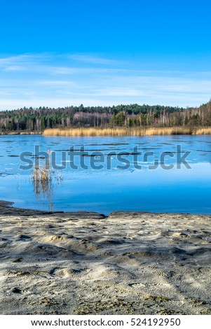 Thaws of frozen lake, melting ice in early spring or late winter, landscape