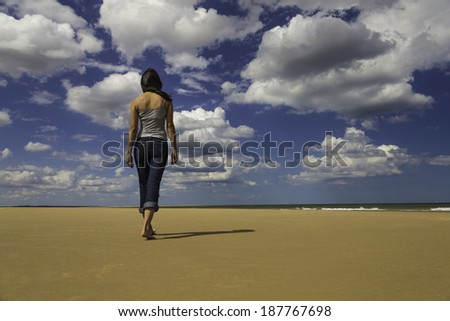 The a young woman walking on the sand of a sunny beach. - stock photo