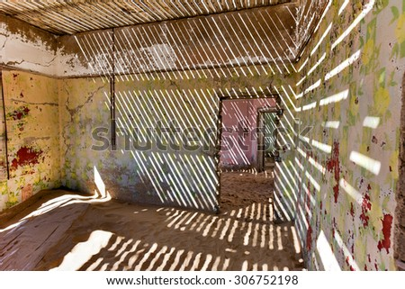The abandoned ghost diamond town of Kolmanskop in Namibia, which is slowly being swallowed by the desert. - stock photo
