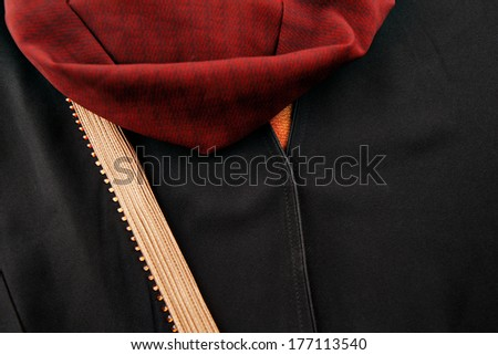 The abaya is the outer cloak like garment worn by Muslim women in the Middle East, Indonesia and North Africa. It is usually black and often has ornate embroidered colorful trim. - stock photo