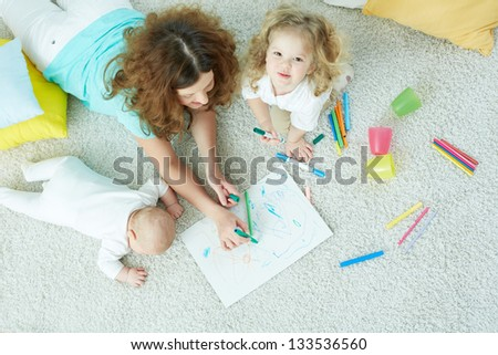 The above view of a happy family lying on the floor and drawing - stock photo
