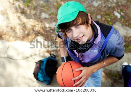 The above view of a smiling teen boy holding a basket-ball - stock photo