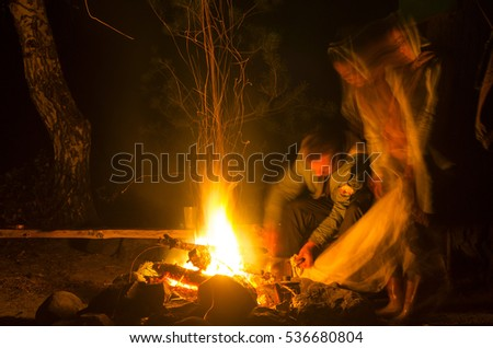 The abstract photograph of lights campsites with fire and silhouettes of people. Soft focus.