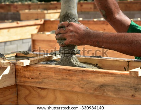 The action packed pouring of cement to create a tie beam during construction of a concrete block wall.  It is a team effort. - stock photo