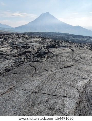 The active lava flow from a new crater on the slopes of volcanoes Tolbachic, on background volcano Bolshaya Udina - Kamchatka, Russia - stock photo