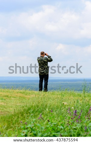 The adult man in a camouflage looks in the binocular at the nature