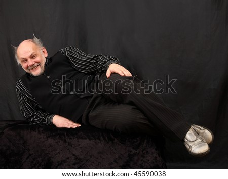 The adult man lays on a black background and smiles