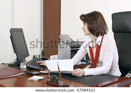 The adult woman the chief works at office behind a table