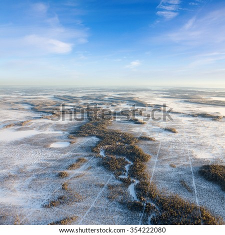 The Aerial view the river on snow-covered forest plain in time of cold winter day. Network of seismic tracks of geophysical exploration in Western Siberia, top view - stock photo