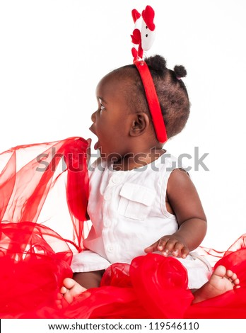 The african baby girl is dressed for the Christmas season and playing with the organza. - stock photo
