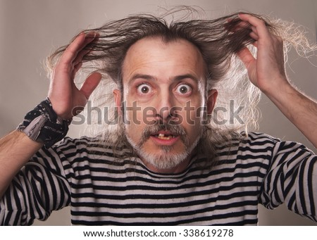 the aged man with crazy expressive face  in a sailor isolated on the white background - stock photo