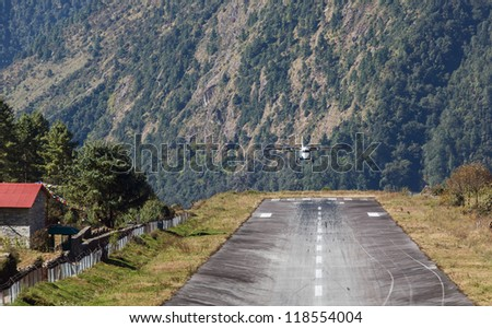 The aircraft is landing on the runway of the Tenzing-Hillary airport Lukla - Nepal, Himalayas - stock photo