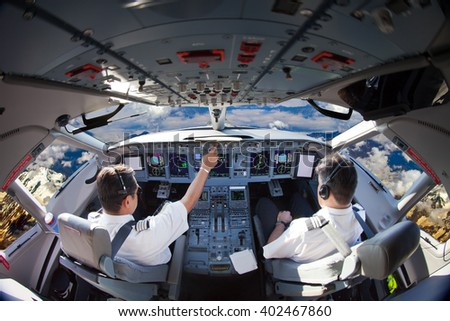 The Aircraft pilots at work. Plane is flying over the mountains. View from the cockpit.  - stock photo