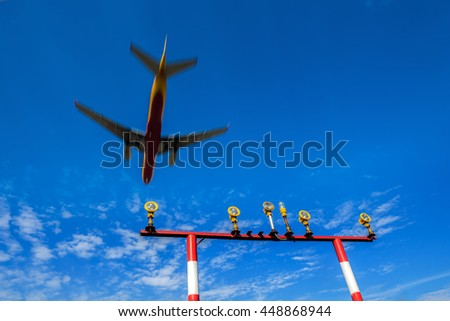 The airplane landed at the airport flying over the landing lights masts - stock photo