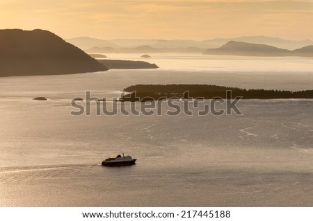 The Alaska Ferry. The Alaska ferry en route to Ketchikan and beyond from Bellingham, Washington. Sunset over the San Juan Islands of Puget Sound in western Washington State, USA.  - stock photo