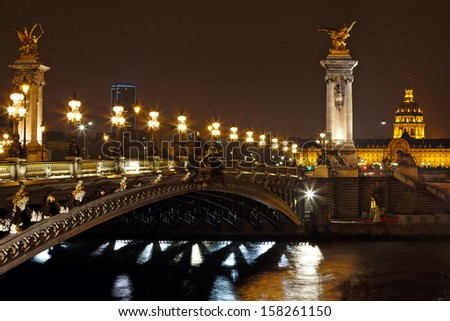 The Alexander III bridge across river seine at night in Paris, France - stock photo
