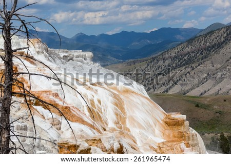 The amazing Mammoth Hot Springs in Yellowstone National Park with steam rising from the colorful staircase formation, distant high mountains, and a fluffy cloud sky. - stock photo