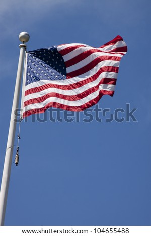 The American flag waving against a blue sky background - stock photo