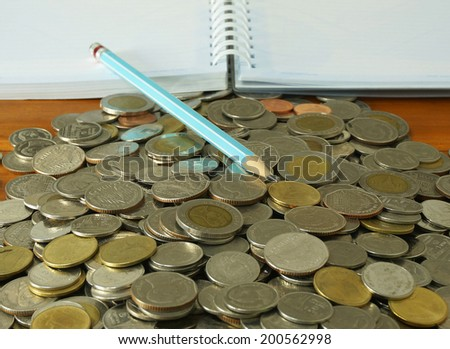 The amount of money placed on the table. A notebook and pencil to note the increase of money.                               - stock photo