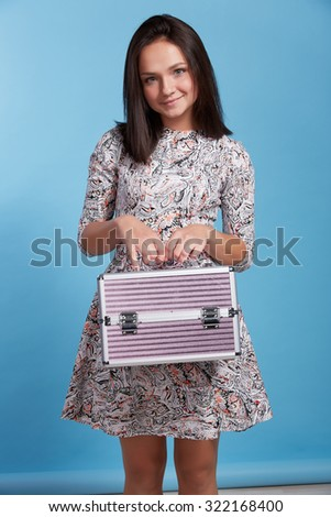 the amusing brunette with a suitcase for cosmetics