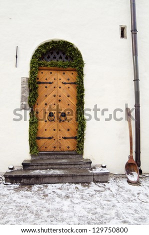The ancient door decorated to Christmas - stock photo