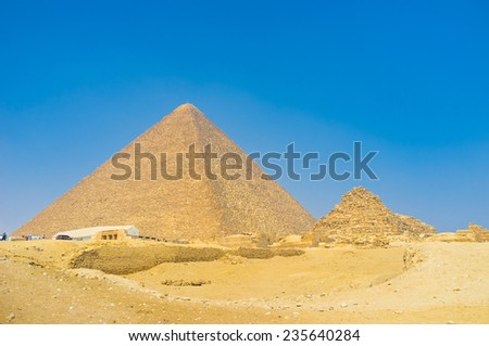 The ancient Pyramids of Giza surrounded by the ruins of the temples and desert sands, Egypt. - stock photo