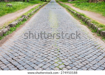 "The ancient road of ""Via Appia Antica"" in Rome old town, topped with interlocking stones, one of the earliest and strategically most important Roman roads. It connected Rome to southeast Italy. - stock photo"