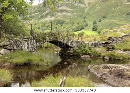 The ancient Slaters Bridge crossing the River Brathay in Little Langdale in the heart of the English Lake District in Cumbria. - stock photo