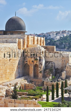 The ancient walls of Jerusalem, lit morning sun. Gray dome of the Al-Aqsa Mosque on the Temple Mount in Jerusalem - stock photo