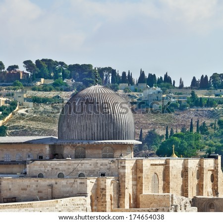 The ancient walls of Jerusalem, lit morning sun. The dome of the Al Aqsa Mosque on the Temple Mount in Jerusalem  - stock photo