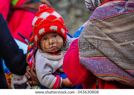 THE ANDES, PERU - MAY 30, 2012: Quechua baby looking in a village in the mountains of The Andes over Ollantaytambo, Peru - stock photo