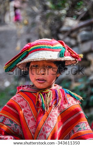 THE ANDES, PERU - MAY 30, 2012: Quechua boy in a hat in a village in the mountains of The Andes over Ollantaytambo, Peru - stock photo