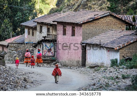 THE ANDES, PERU - MAY 30, 2012: Quechua family going home in a village in the mountains of The Andes over Ollantaytambo, Peru - stock photo