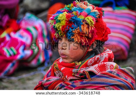 THE ANDES, PERU - MAY 30, 2012: Quechua girl looking in a village in the mountains of The Andes over Ollantaytambo, Peru - stock photo