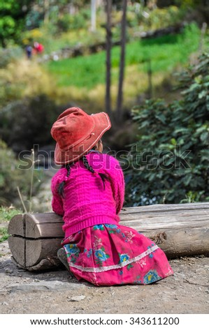 THE ANDES, PERU - MAY 30, 2012: Quechua girl with hat in a village in the mountains of The Andes over Ollantaytambo, Peru - stock photo