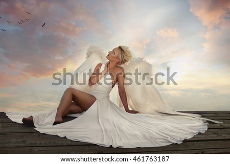 The angel with wings sits on the roof at sunset. Delicate beautiful blonde woman posing with angel wings. Woman Angel with Wings. Fashion White Dress, Fabric Cloth Waving On Wind. Sweet angel.
