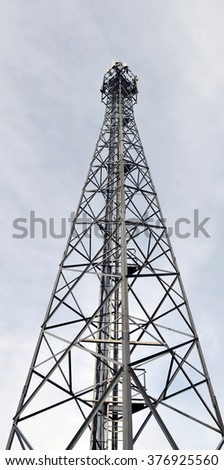 The antenna tower of cell phone close up against the sky. - stock photo