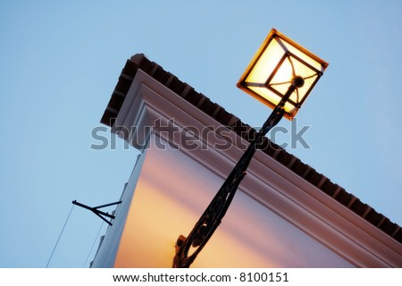 The antique lantern (street lamp) hanging on the (exterior) wall of residential house