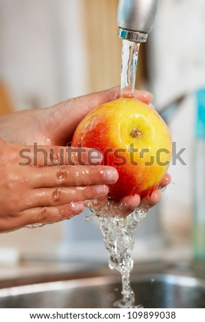 The apple is being washed in the steam of water - stock photo