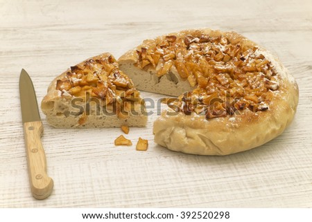 the apple open pie made manually of rough flour is near a knife on a wooden surface