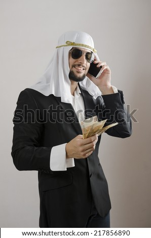 The arab man businessman with money, suit and phone cliche - stock photo