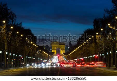 The Arc de Triomphe at the end of the Avenue des Champs-Elysees with the lights from traffic - stock photo