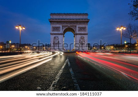 The Arc de Triomphe in Paris at night.