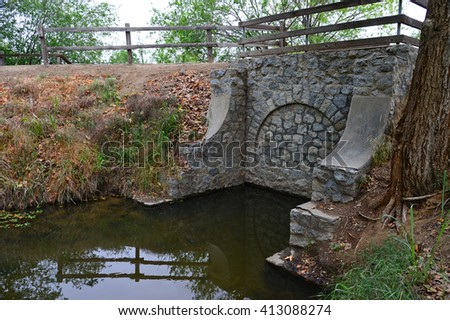The arch on this old bridge has been walled in, the water flow being directed through an underground pipe. - stock photo