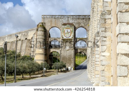 The arches of the Roman Aqueduct Aqueduto da Amoreira in Elvas in Portugal, Detail of the shield of the city - stock photo
