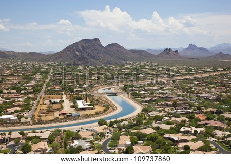 The Arizona Canal winding it's way through a Scottsdale suburb - stock photo