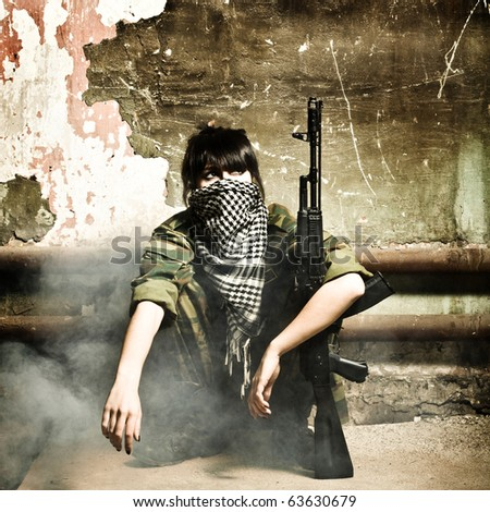 The armed Arabian woman terrorist against old wall studio photo shooting - stock photo